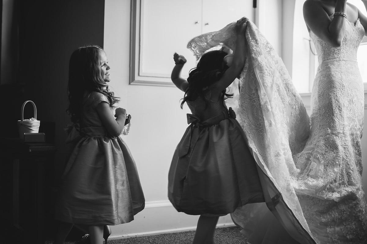 flowergirl hiding under wedding dress