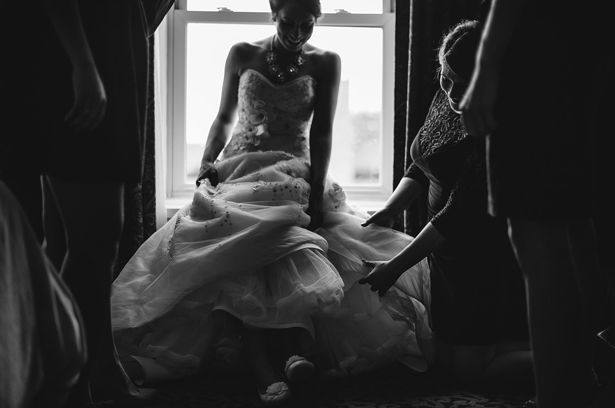 bride getting ready by window by pittsburgh photographers the oberports