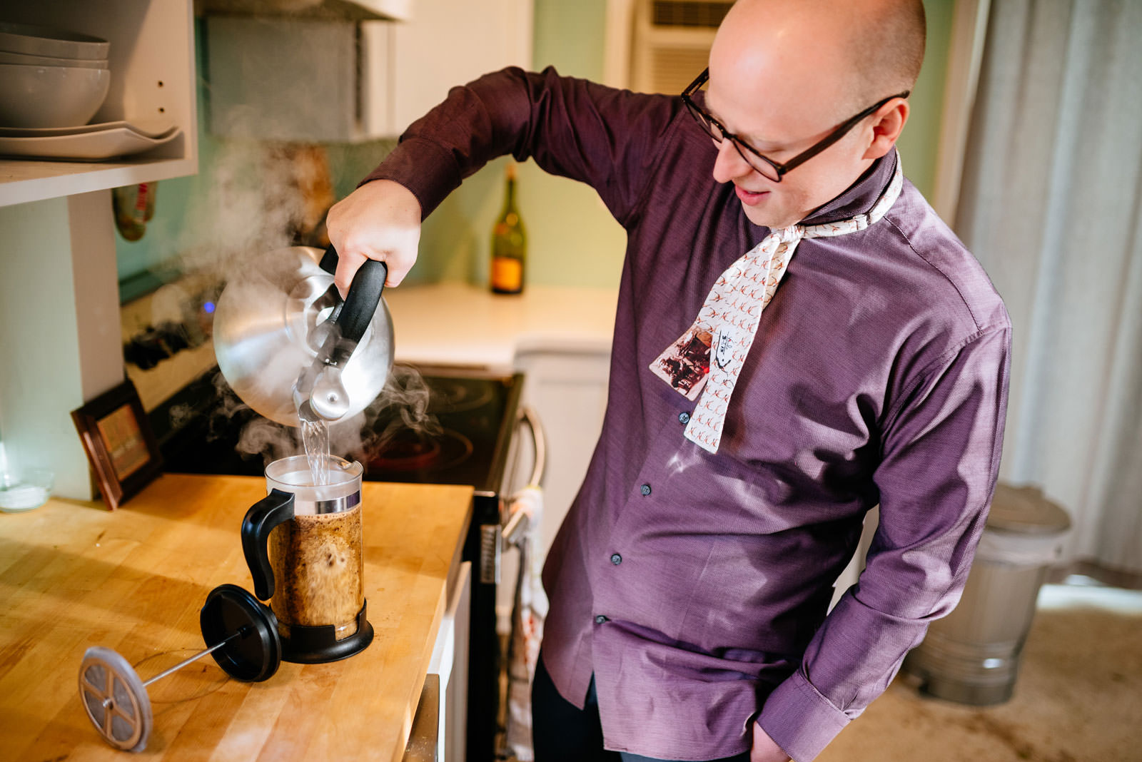 groom making french press coffee while getting ready philadelphia morning elopement