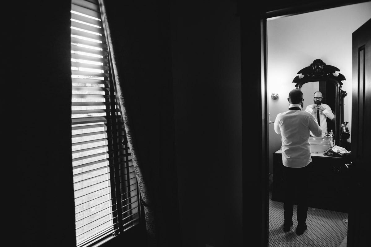 groom putting on tie wv wedding moment