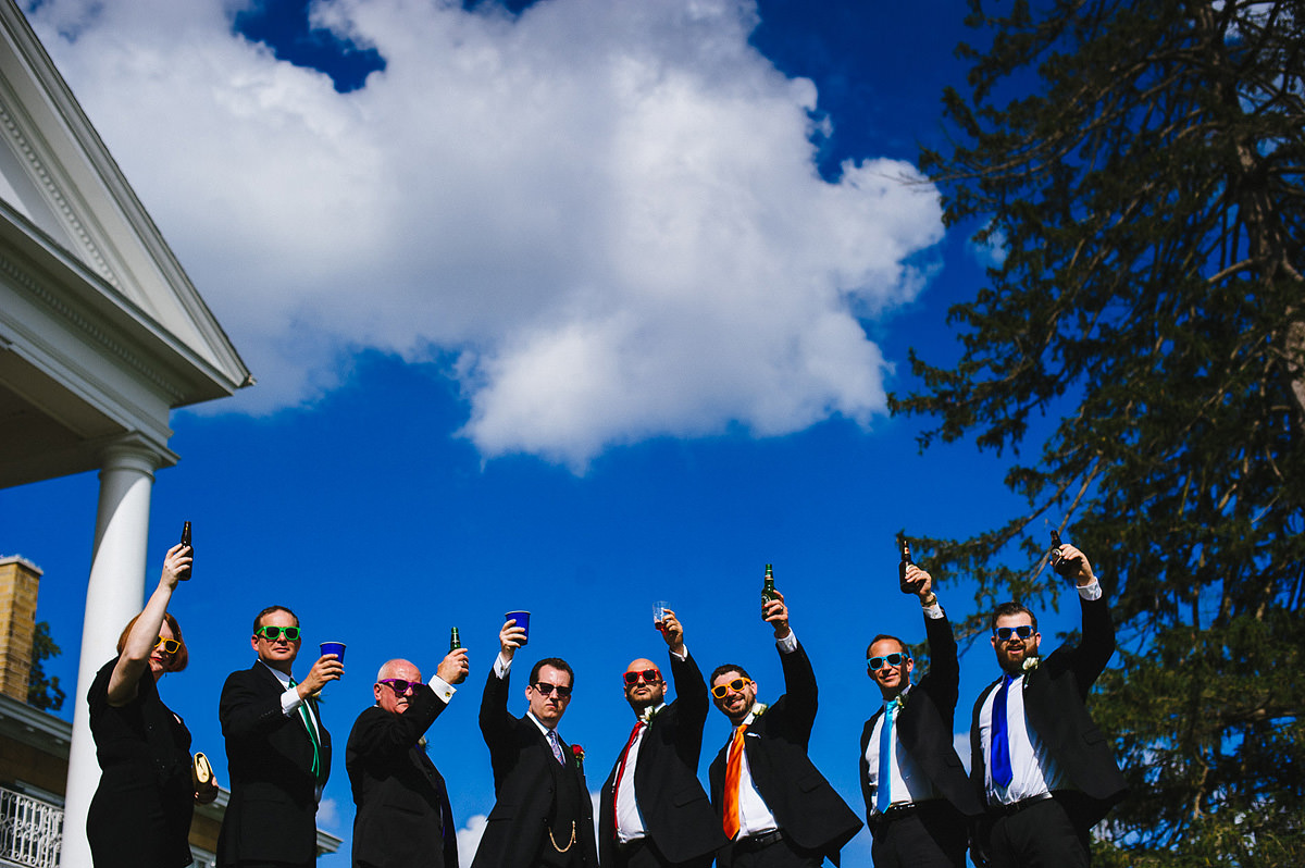 groomsmen photo wearing different colored sunglasses raising glasses to toast