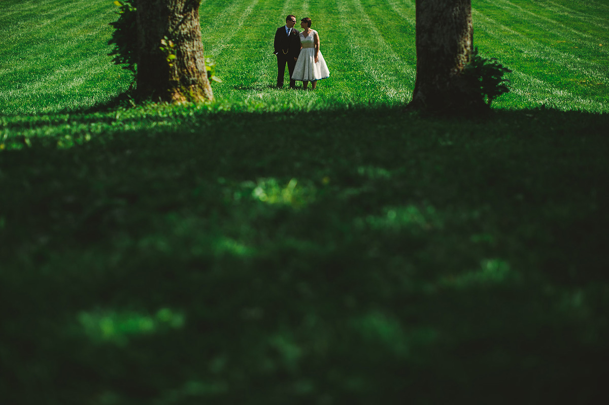 bride and groom portrait between trees at bryn du mansion granville ohio