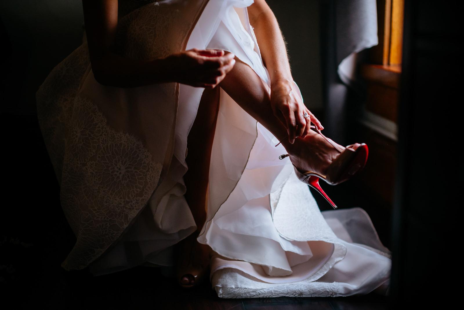 bride putting on louboutin shoes lafayette flats fayetteville wv wedding