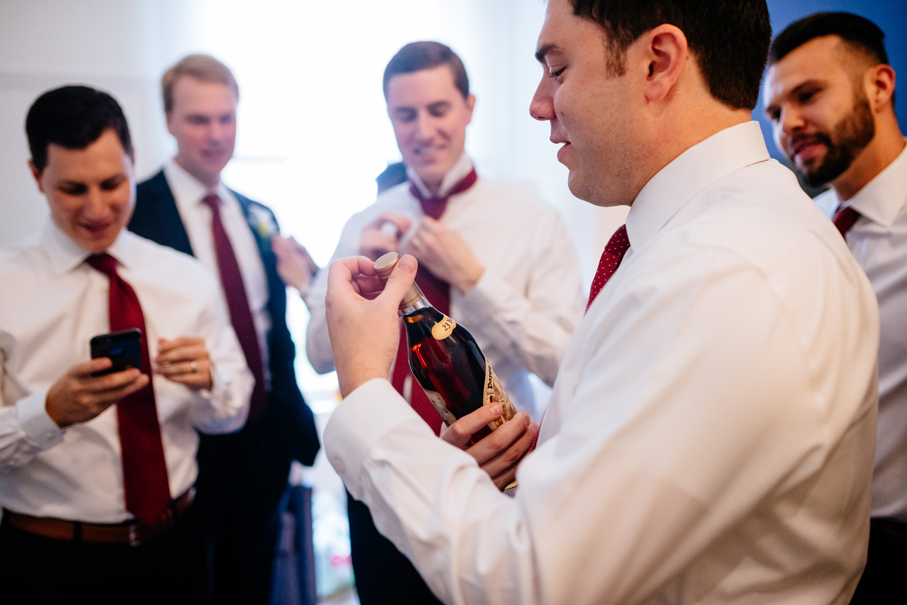 groom opening bottle of pappy whiskey