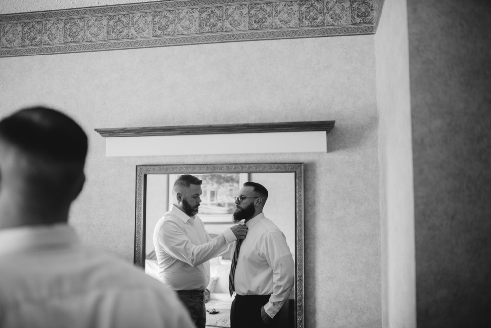 groomsman helps groom with tie