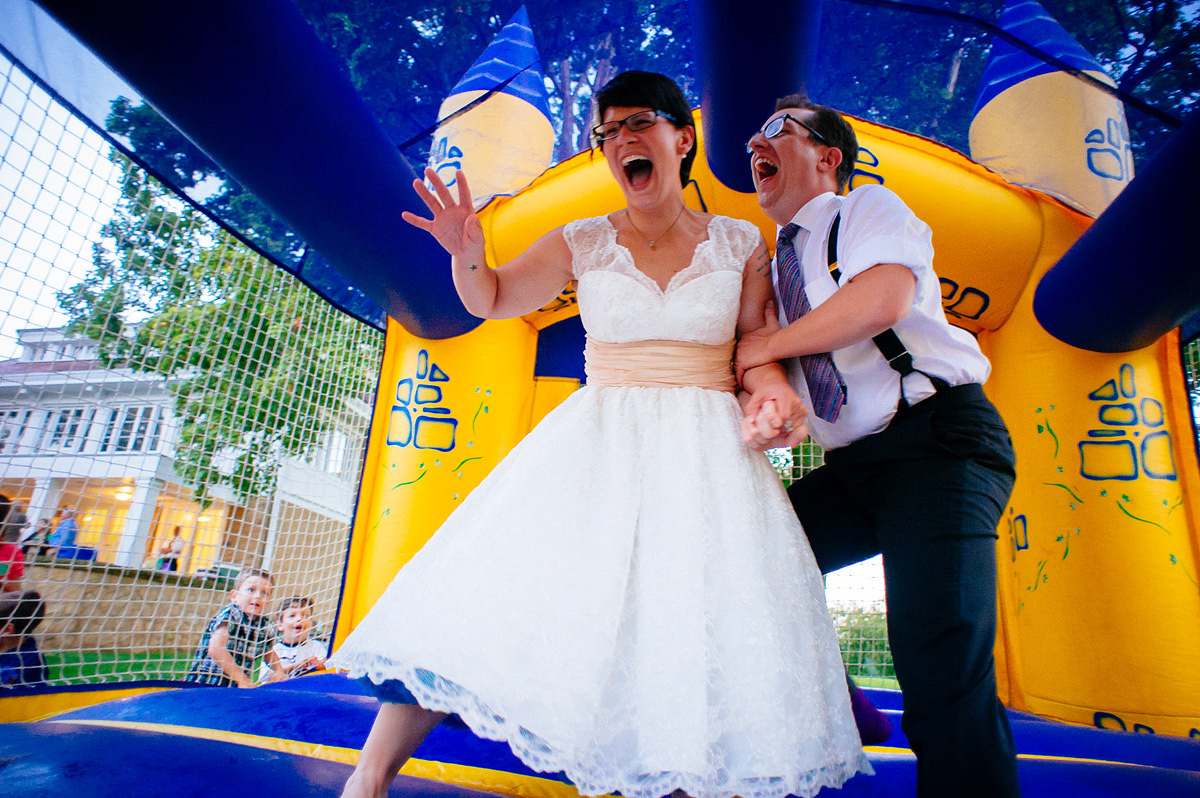 bride and groom jumping in bouncy castle