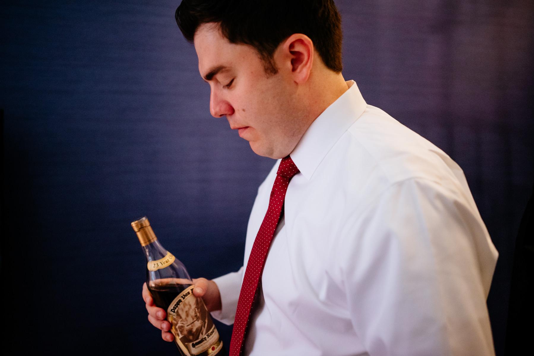 groom with bottle of pappy van winkle whiskey