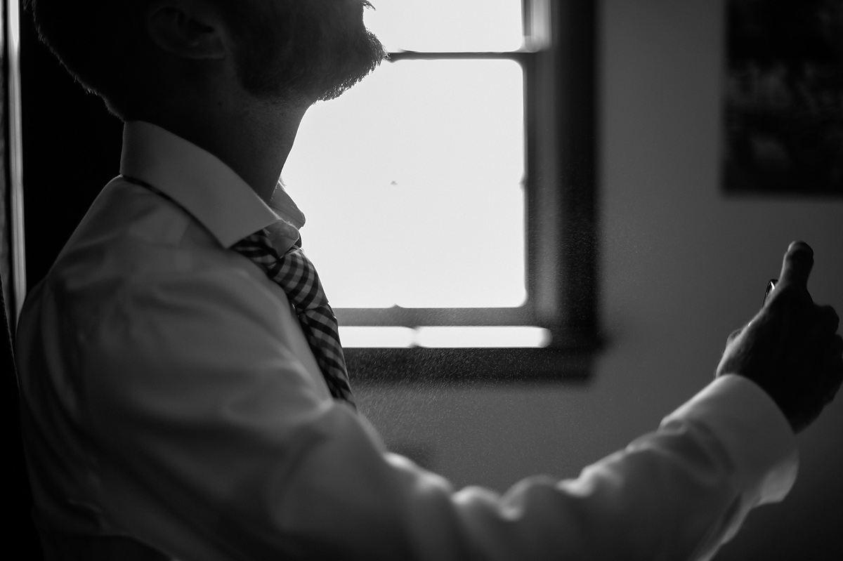 groom spraying cologne