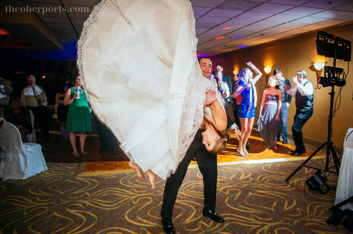 groom flipping bride at reception