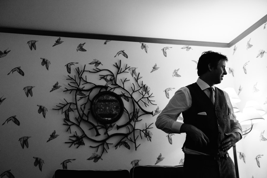 black and white photo of groom getting ready