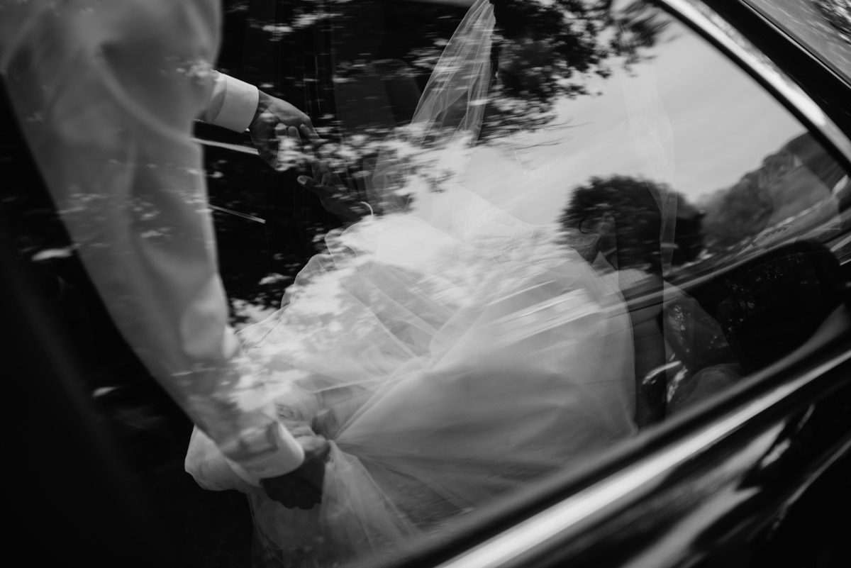 groom helping bride get out of car