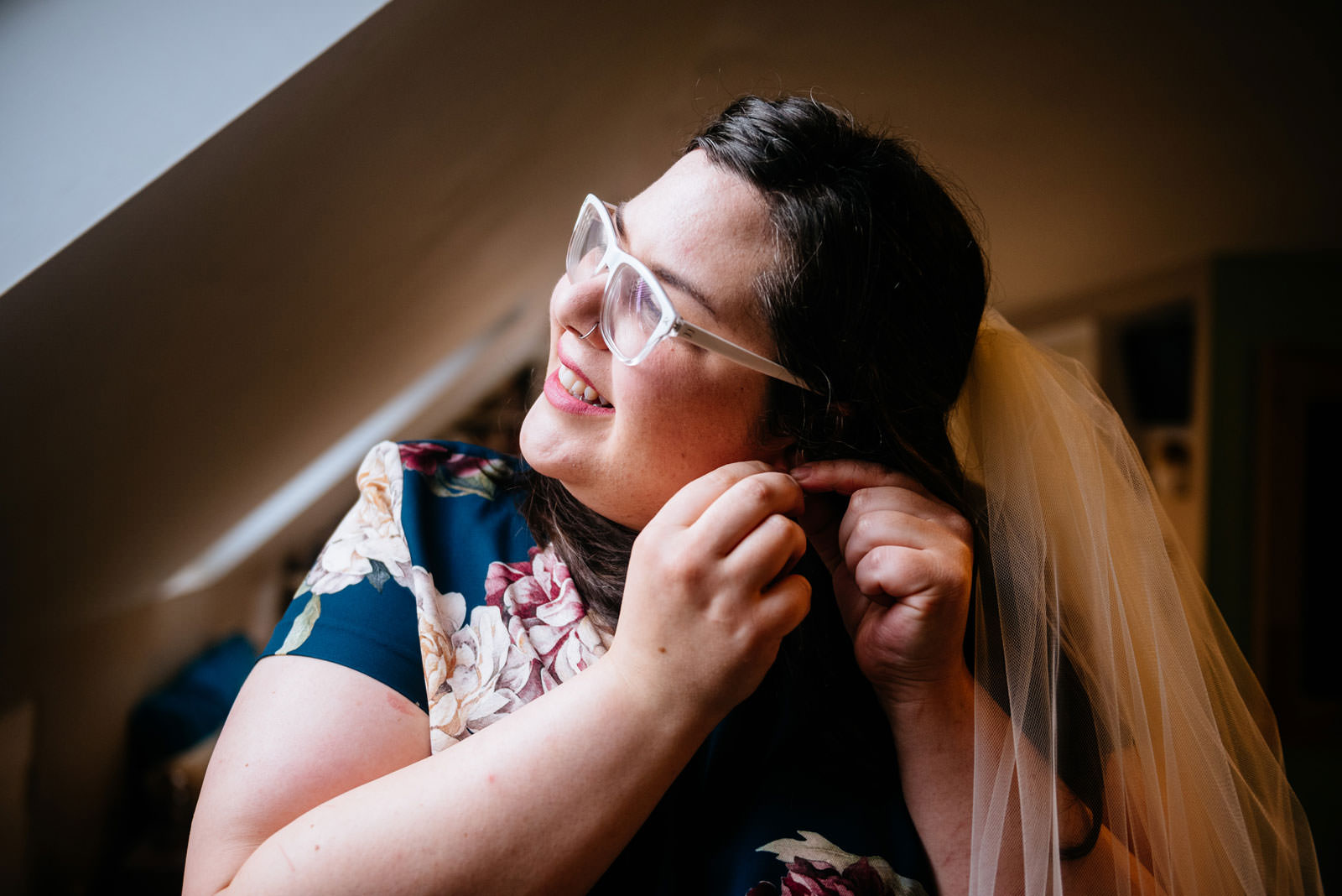 bride putting on earrings in apartment