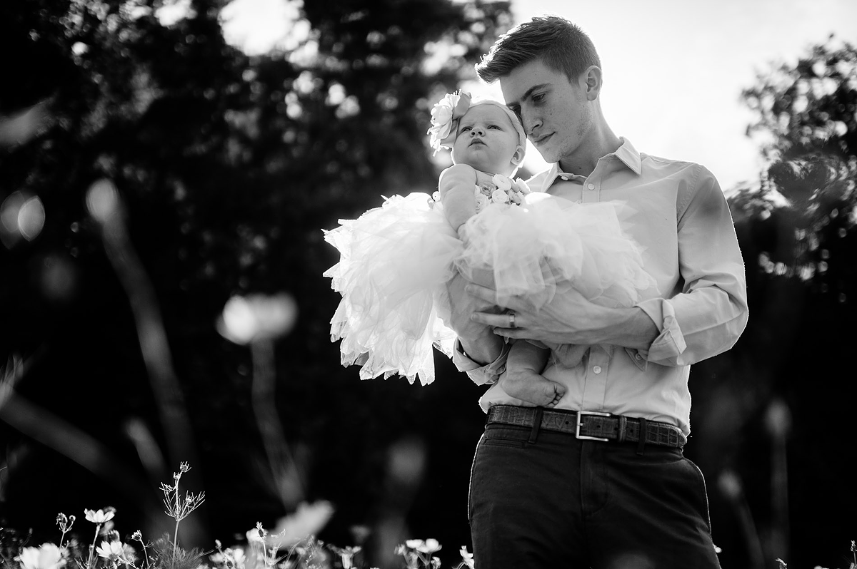 father holding baby girl black and white portrait