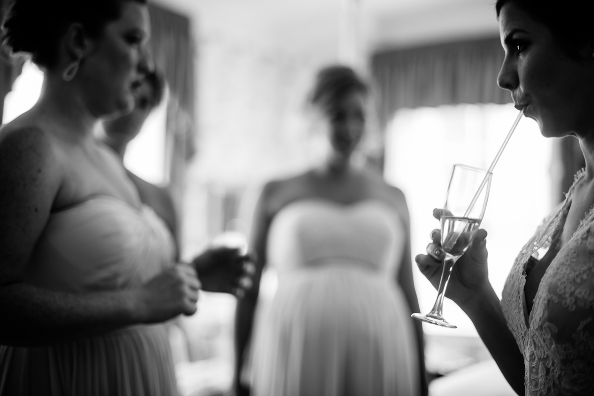 bride sipping champagne with straw