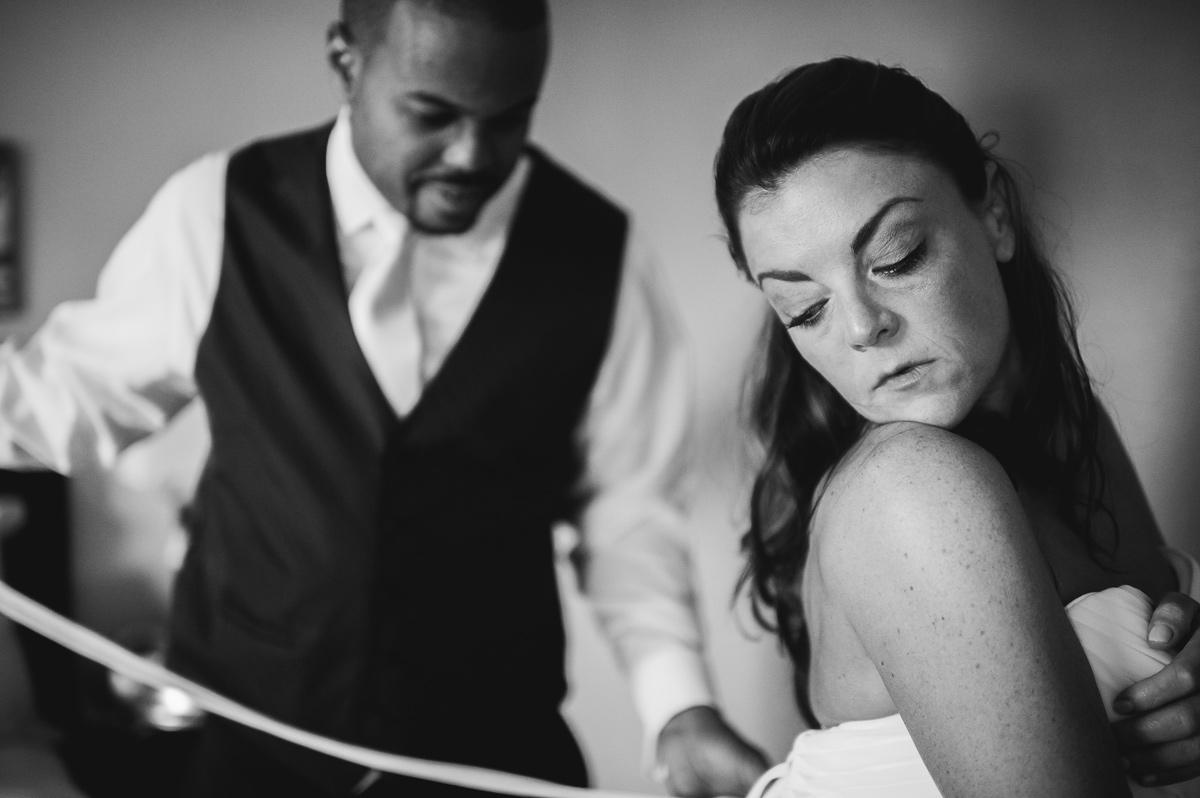 photos of groom helping bride get ready