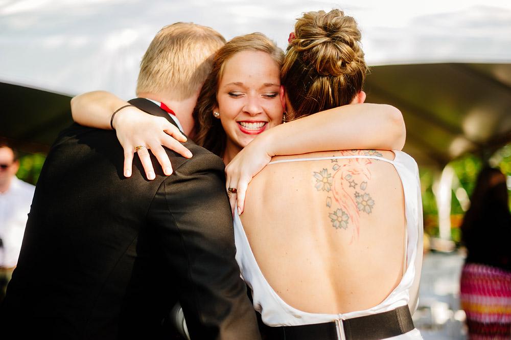 happy wedding guest hugs bride and groom