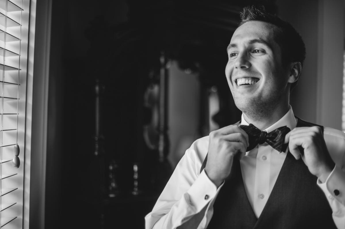 groom adjusting bow tie