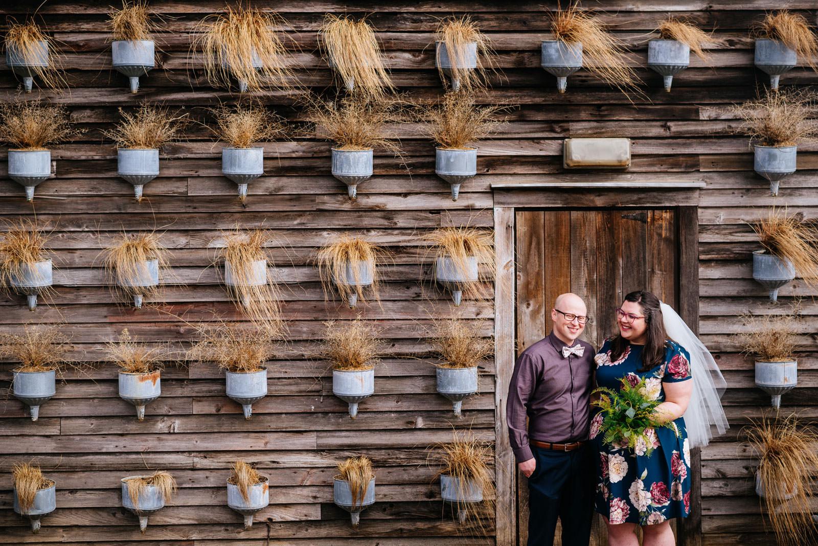 bride groom in doorway surrounded by plants terrain elopement