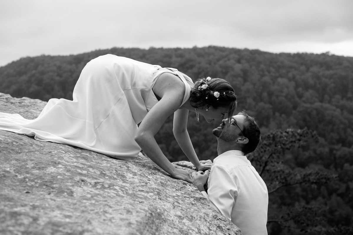 rockclimber wedding bride groom kissing on cliff
