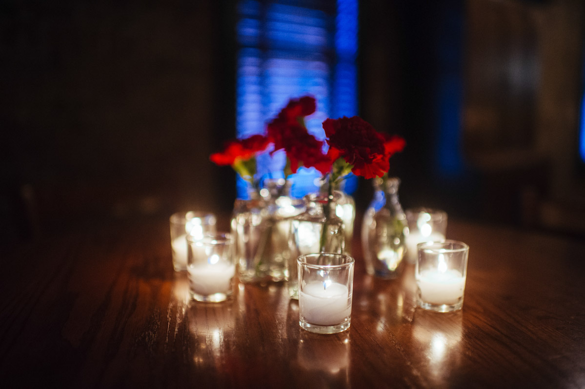 wedding reception details red carnations and candles