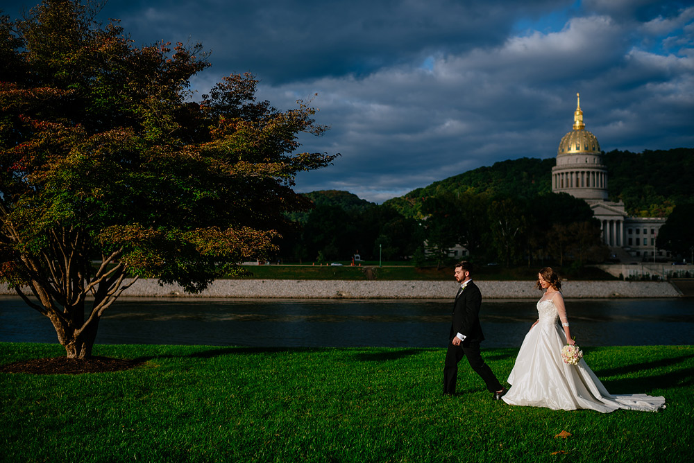 bride and groom walking on UC lawn