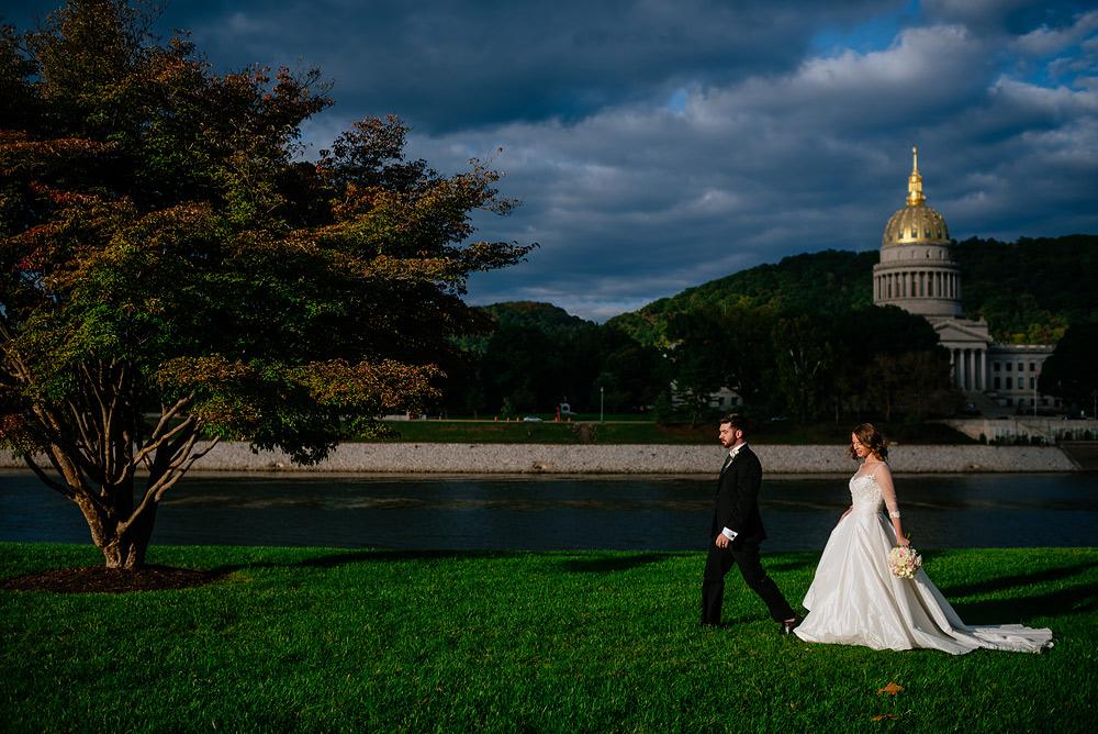 bride and groom walking on UC lawn