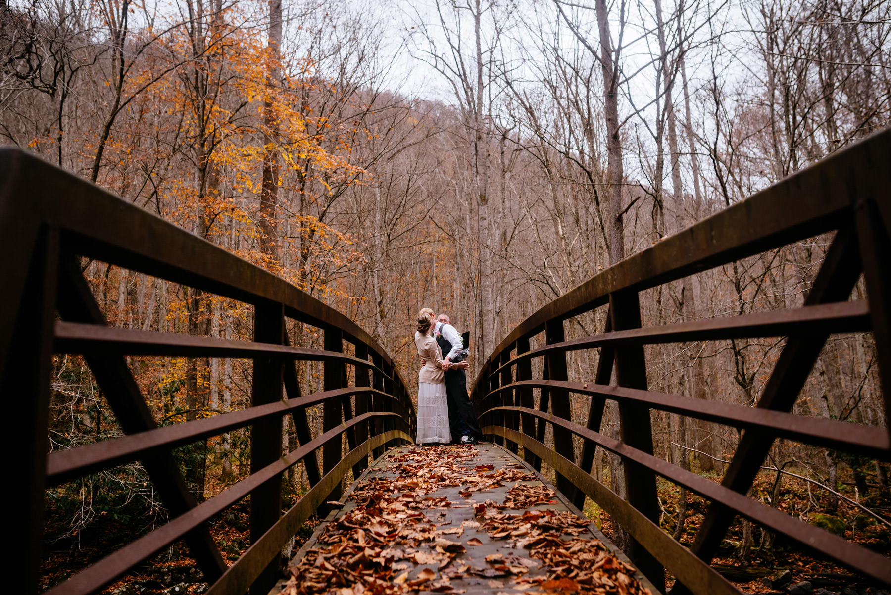 bride groom first kiss on bridge autumn wv hiking elopement