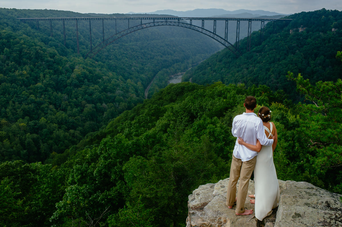 bride groom hug overlooking the new river gorge bridge elopement pictures by best wv wedding photographers the oberports