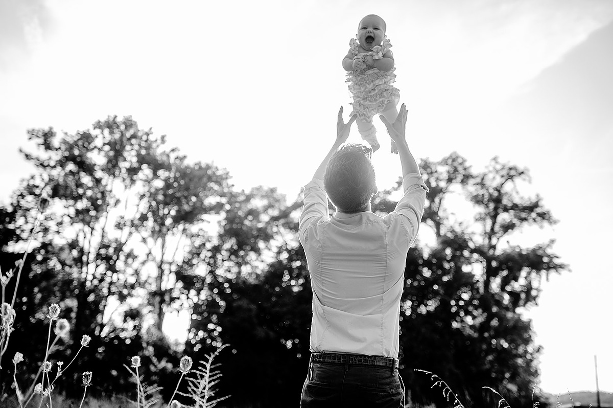 dad tossing baby portrait
