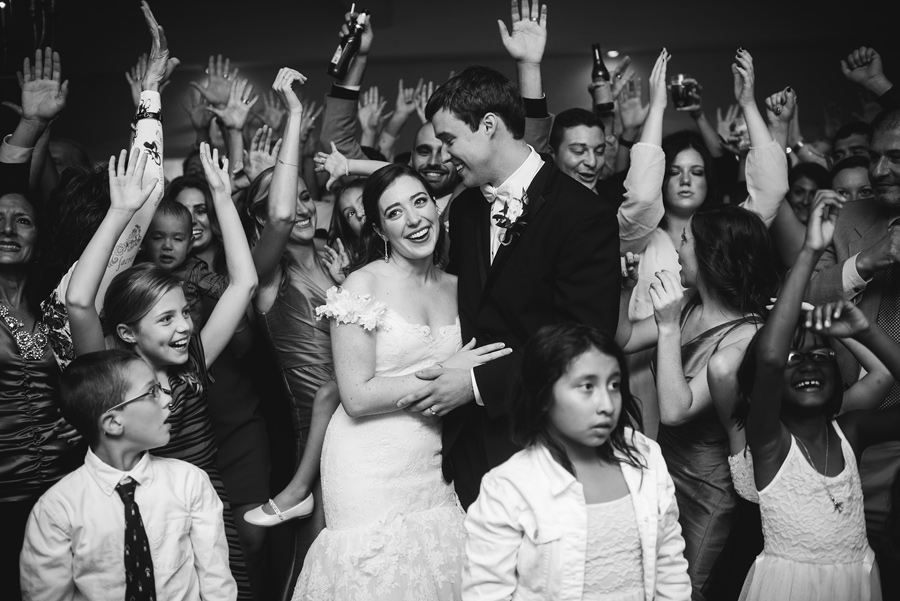 bride and groom surrounded by happy guests at their wedding reception