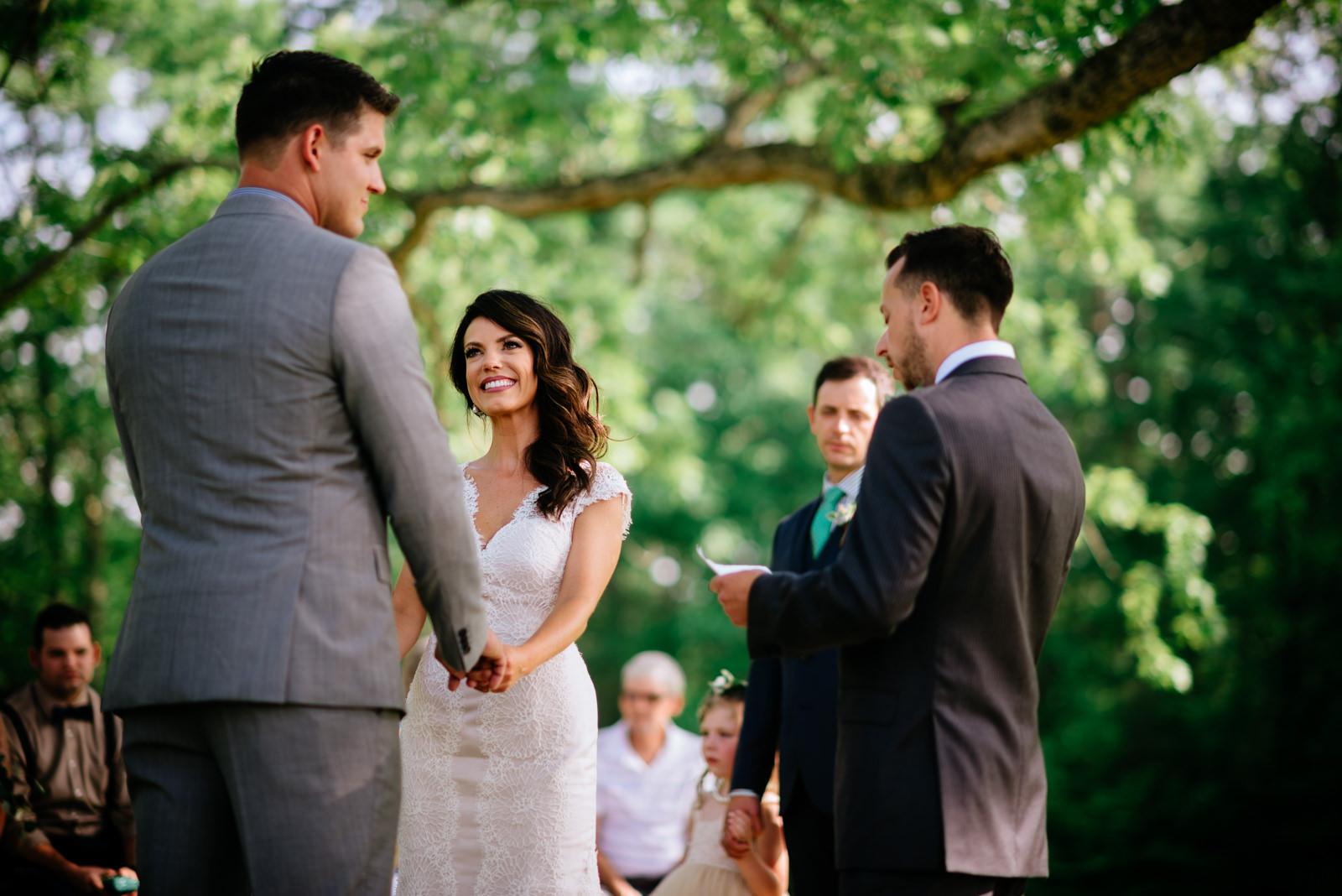 happy bride during ceremony ceremony under white oak tree gaines estate fayetteville wv wedding