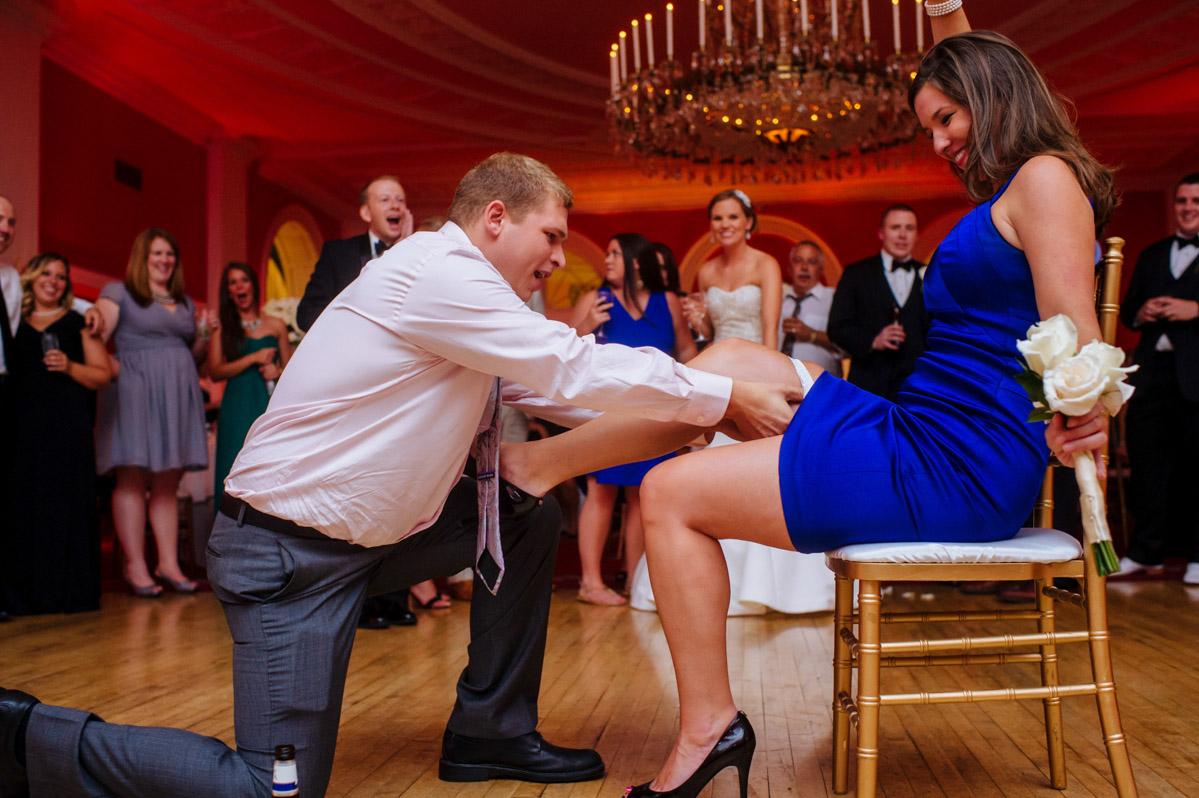 wedding guest putting garter on bouquet toss winner wedding reception