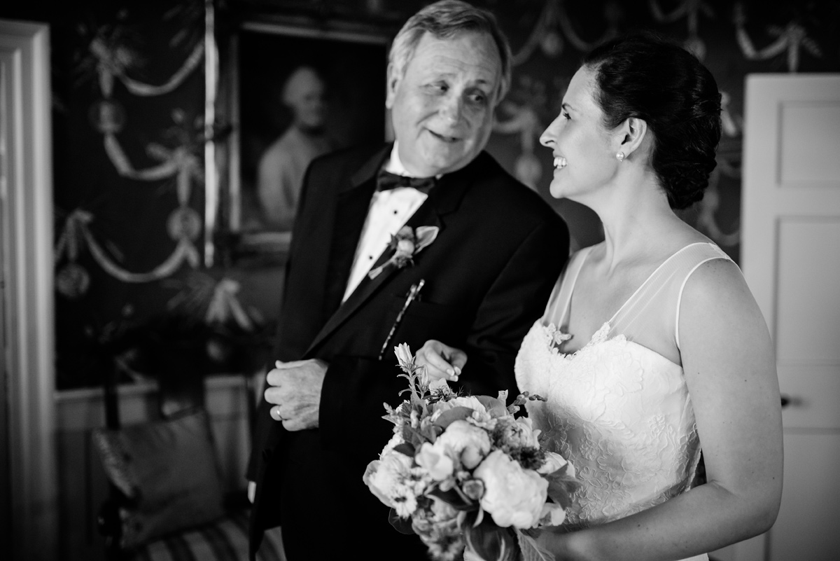bride and father laugh before walking down aisle