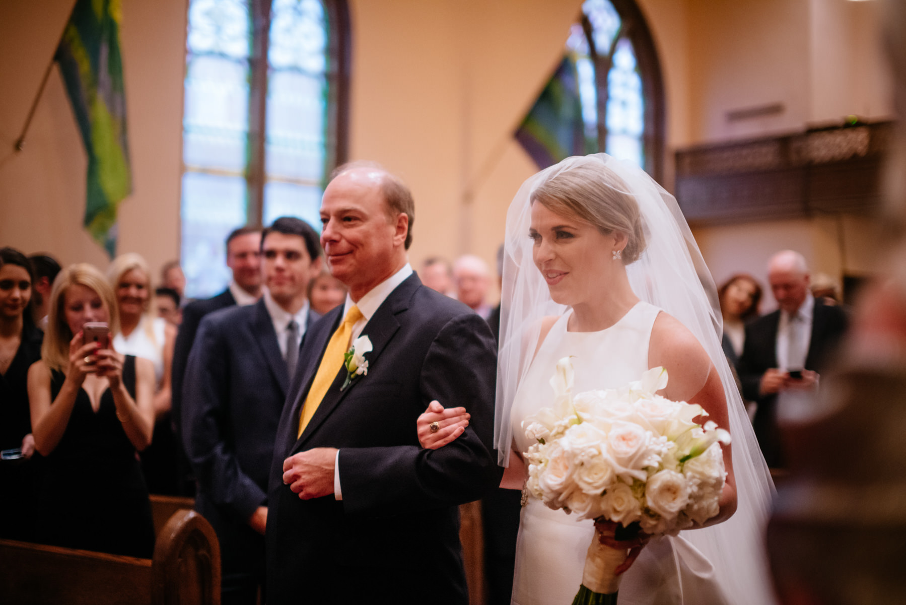 bride and dad walk down ceremony aisle