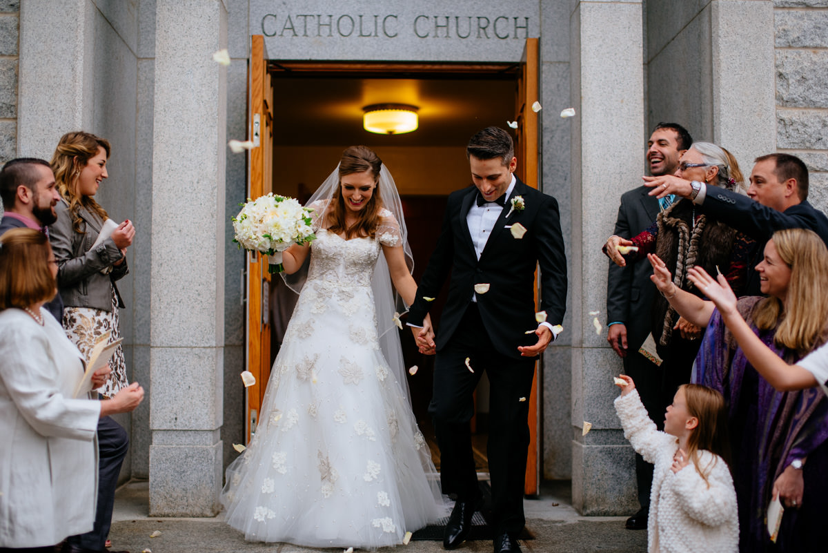 guests throwing flower petals at bride and groom as they leave the church