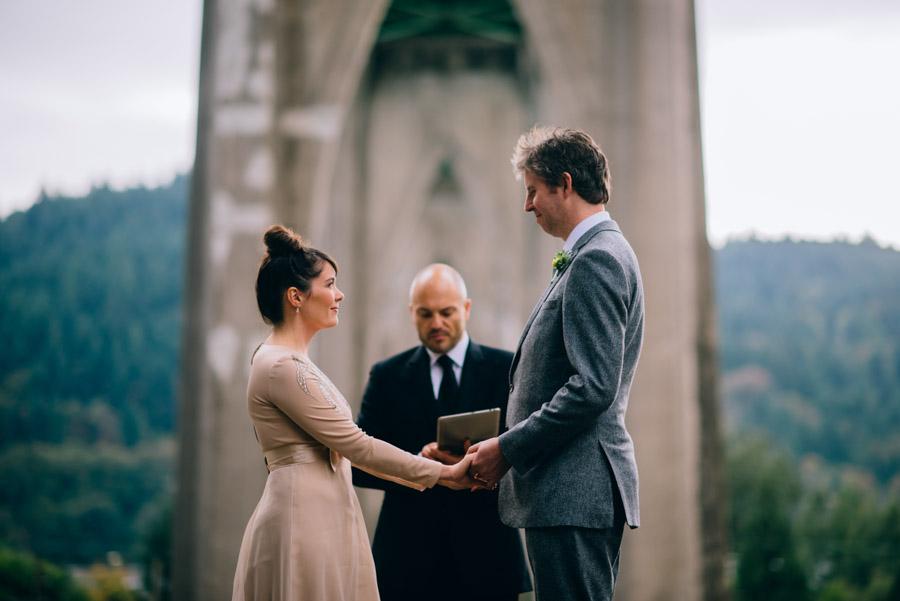 bride groom holding hands during cathedral park ceremony under st johns bridge