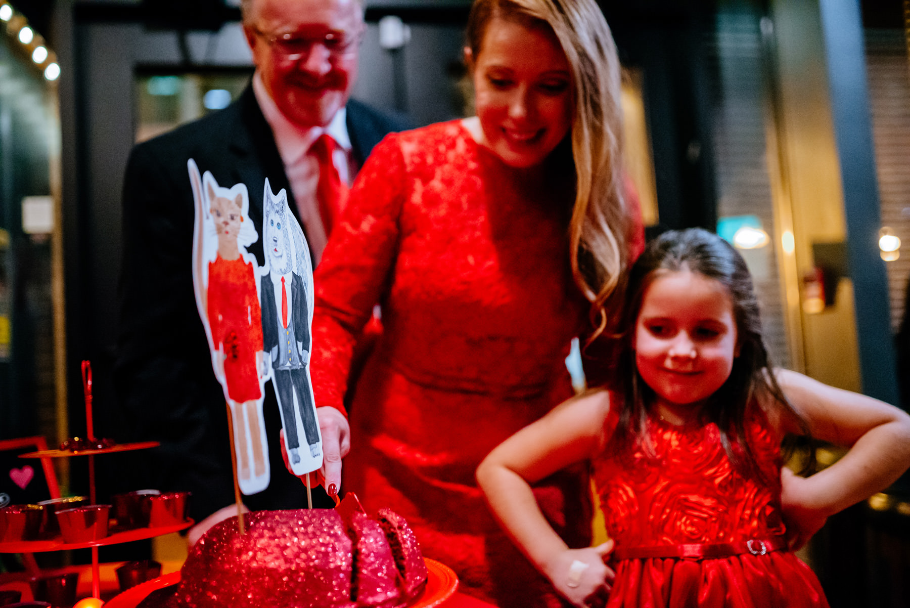 flowergirl inspects wedding cake