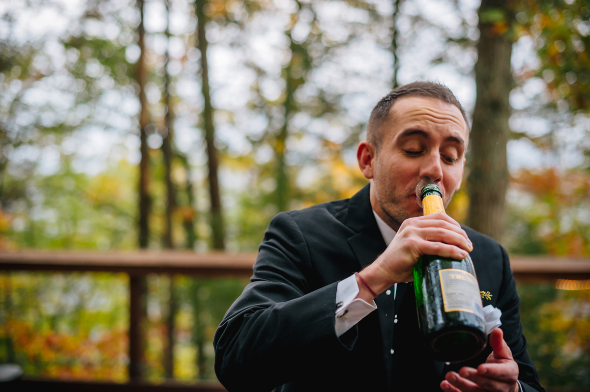 groom chugging champagne from the bottle