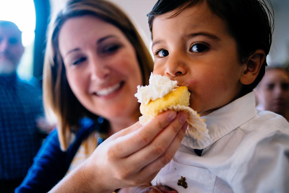 extreme closeup of ring bearer eating cupcake