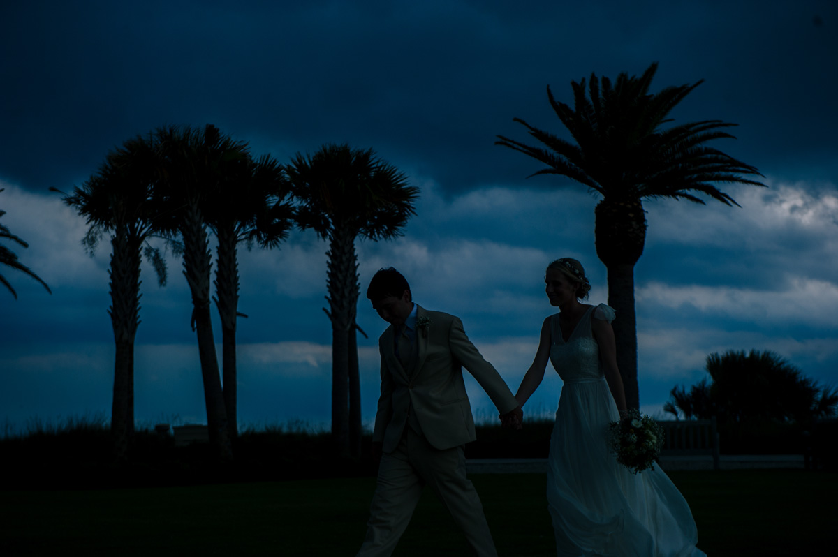 newlyweds running from storm clouds