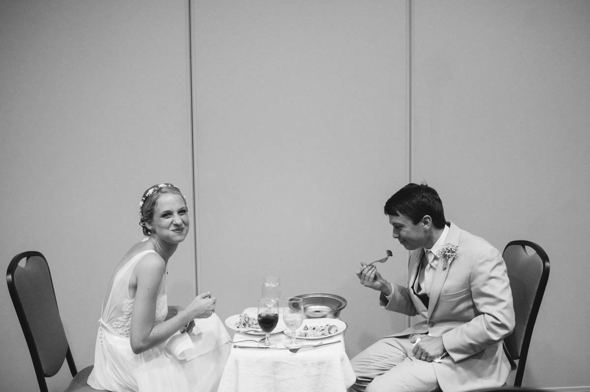 candid photo of bride and groom eating dinner