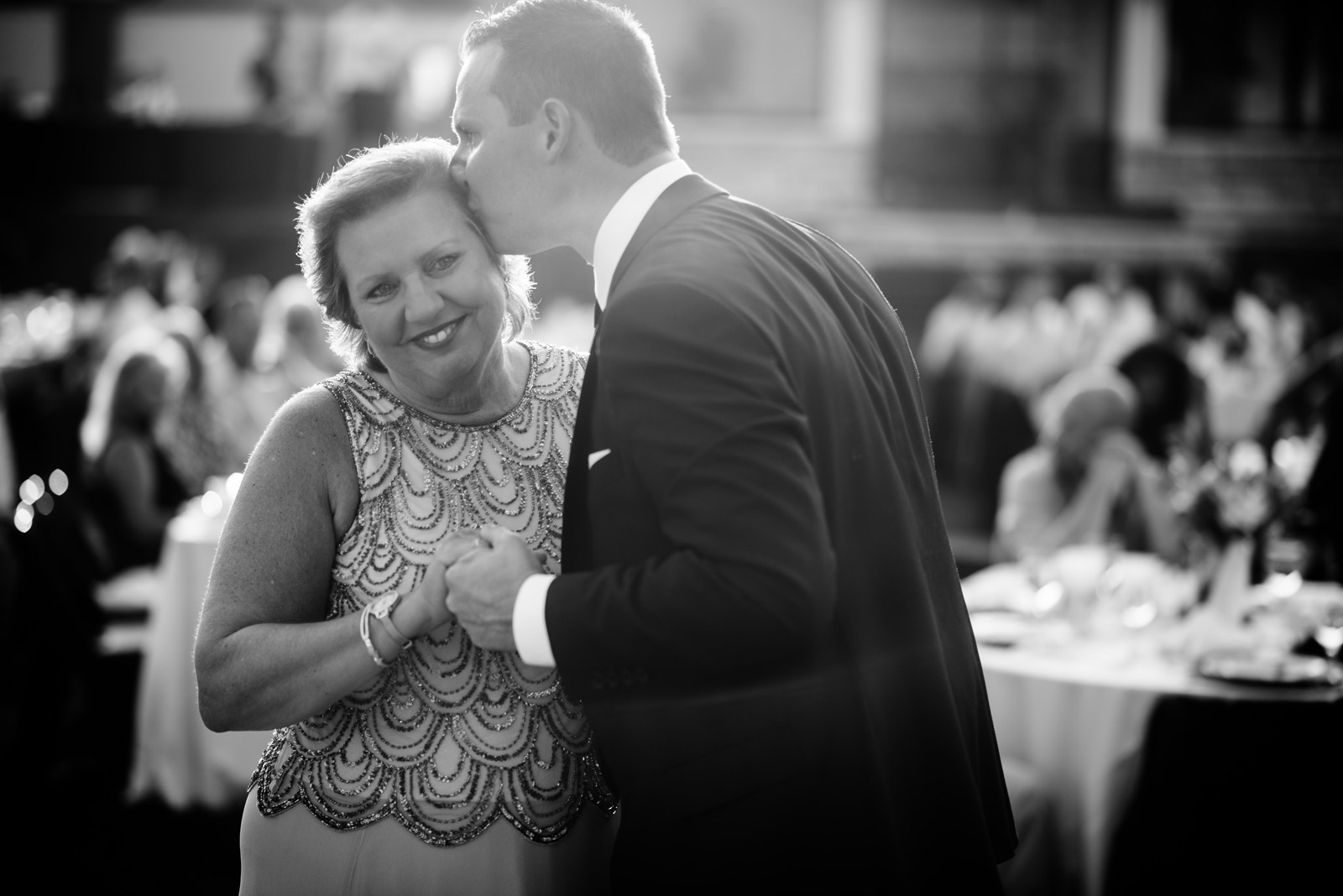 groom kissing mom during mother son dance