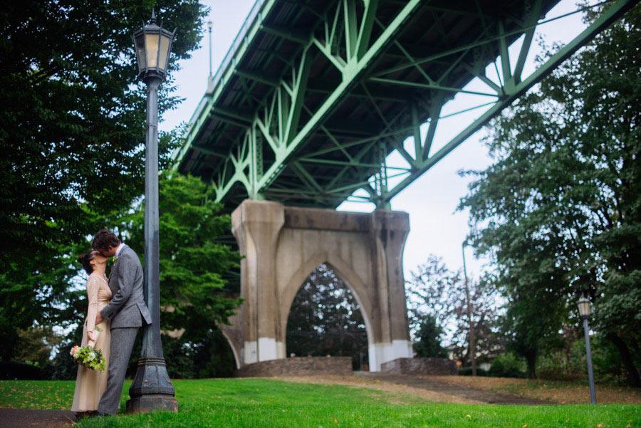 bride groom kissing under cathedral bridge portland oregon