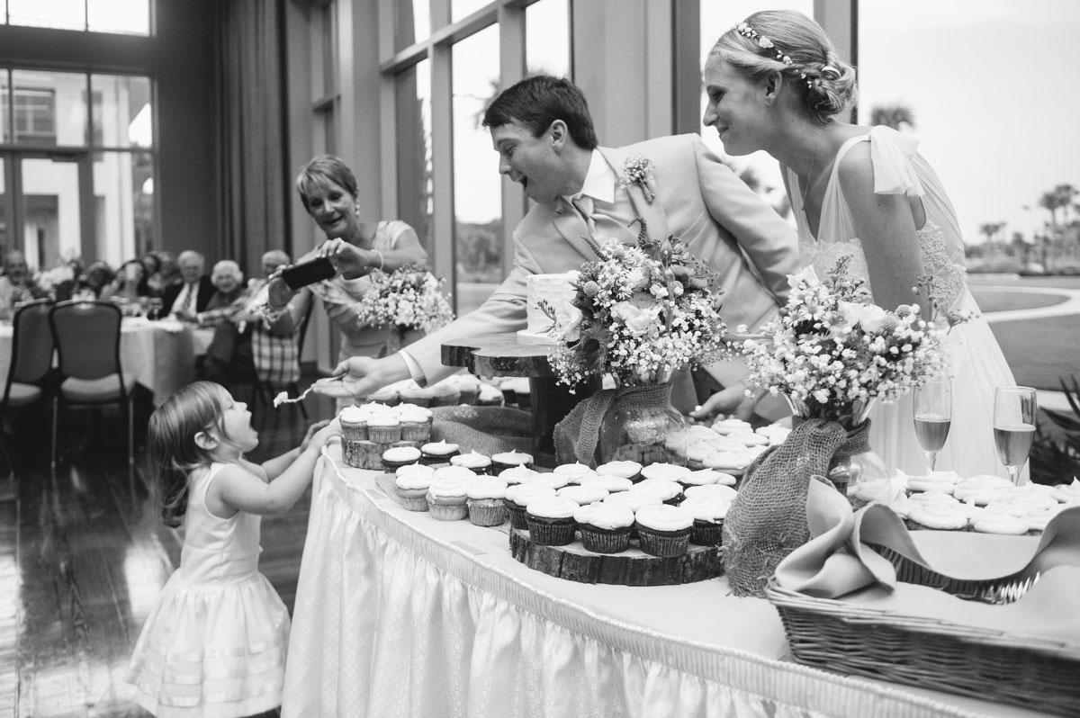 groom feeds flowergirl wedding cake