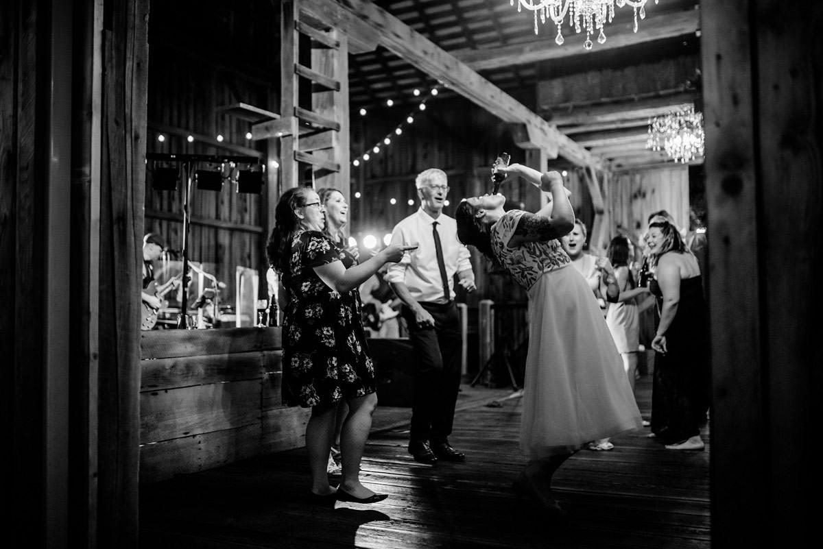 bride chugging beer at wedding reception