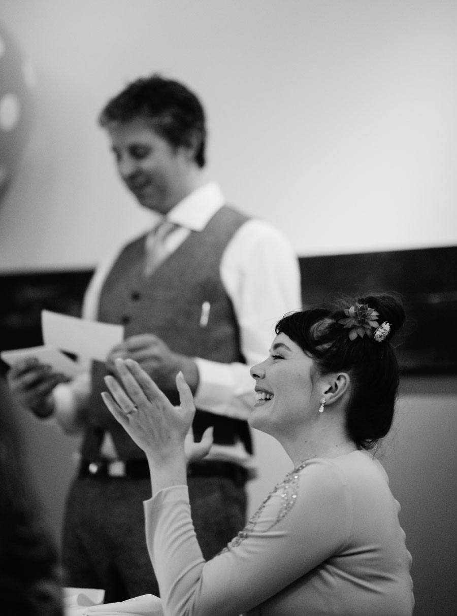 bride clapping happily during wedding reception toasts