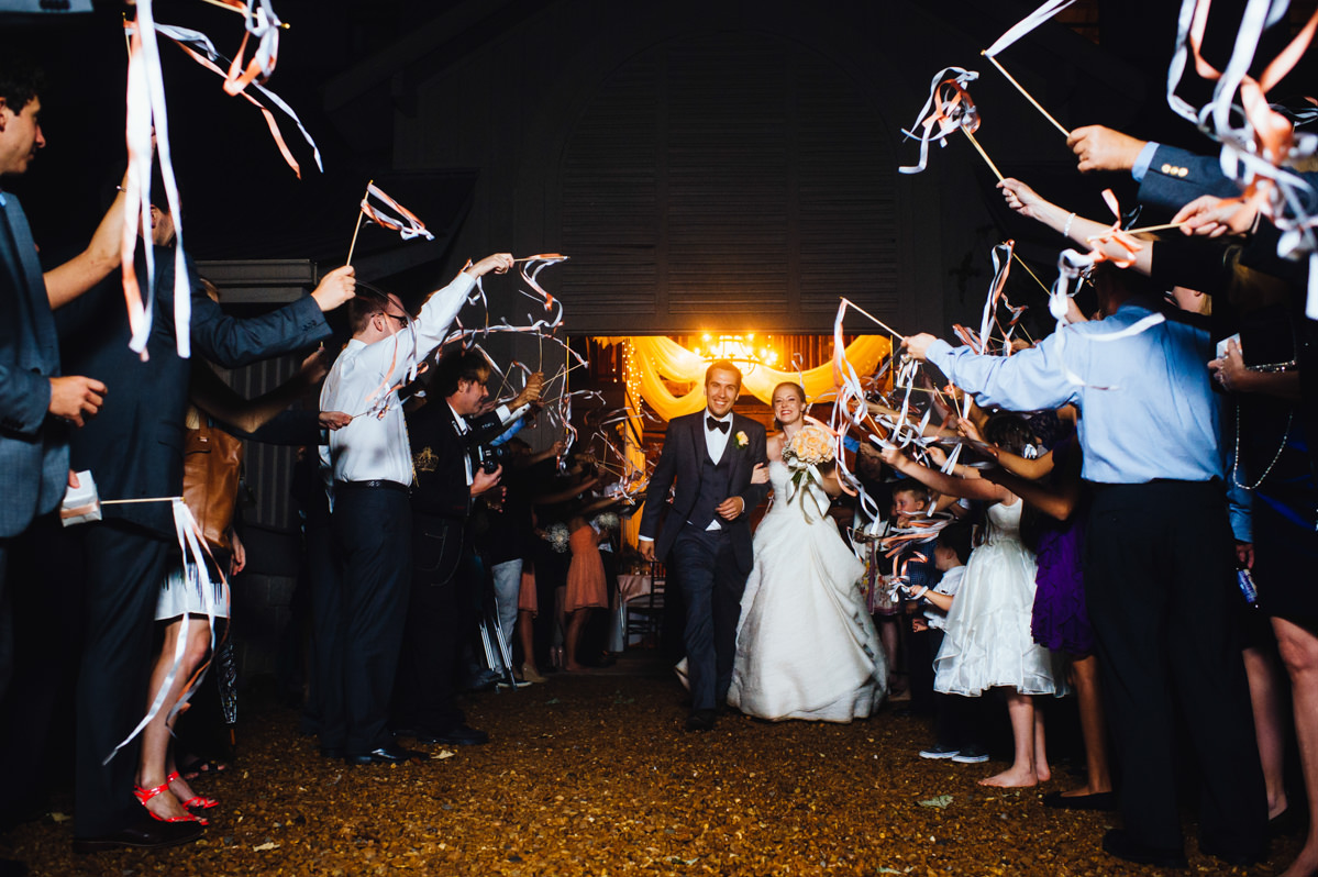 bride and groom exit with ribbons