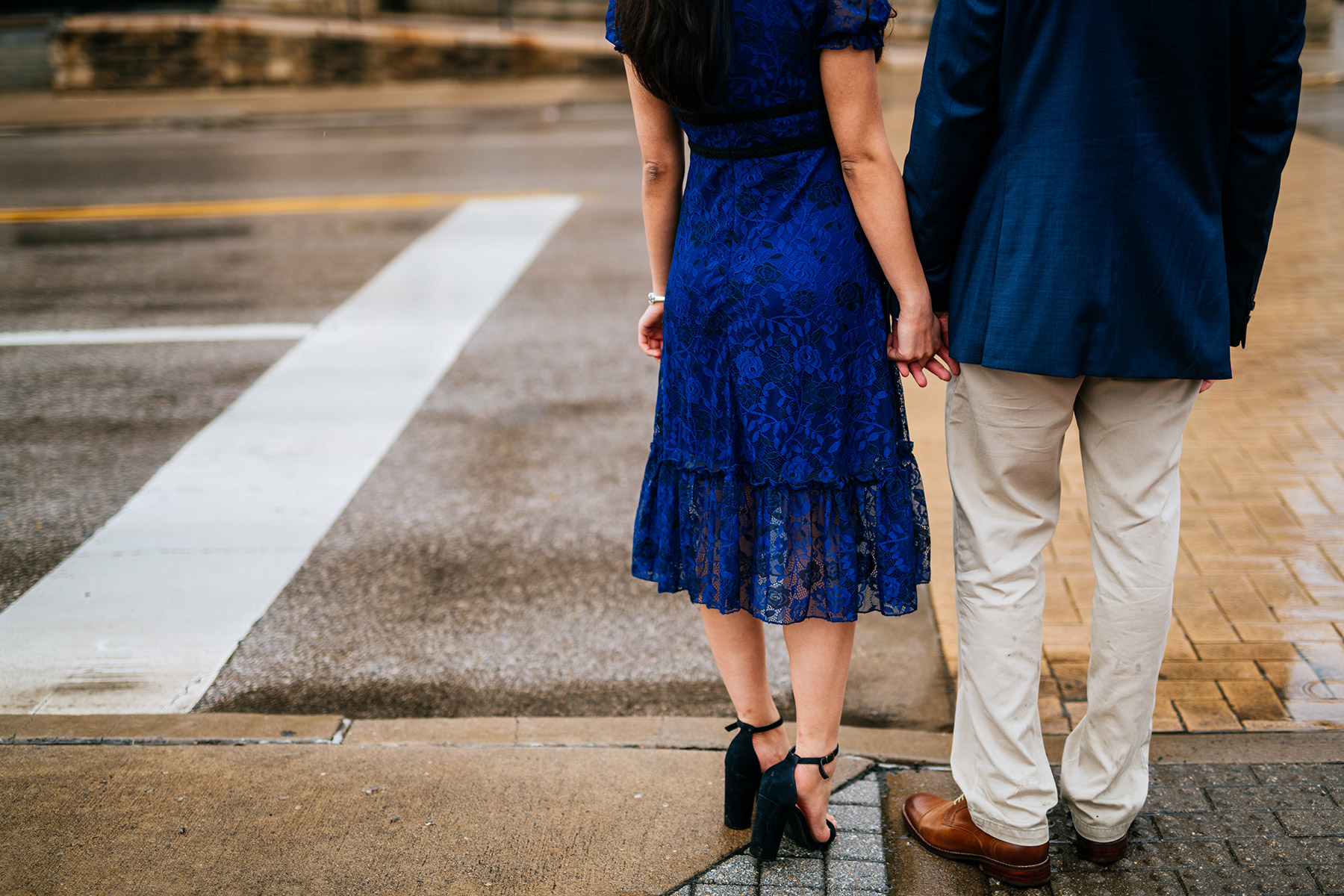 couple holding hands crossing street
