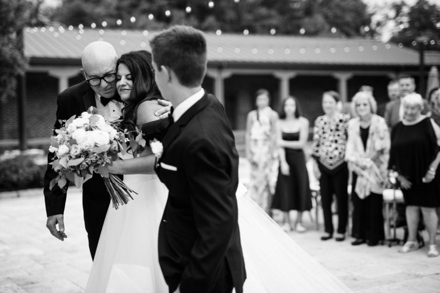 father hugging bride during wedding ceremony