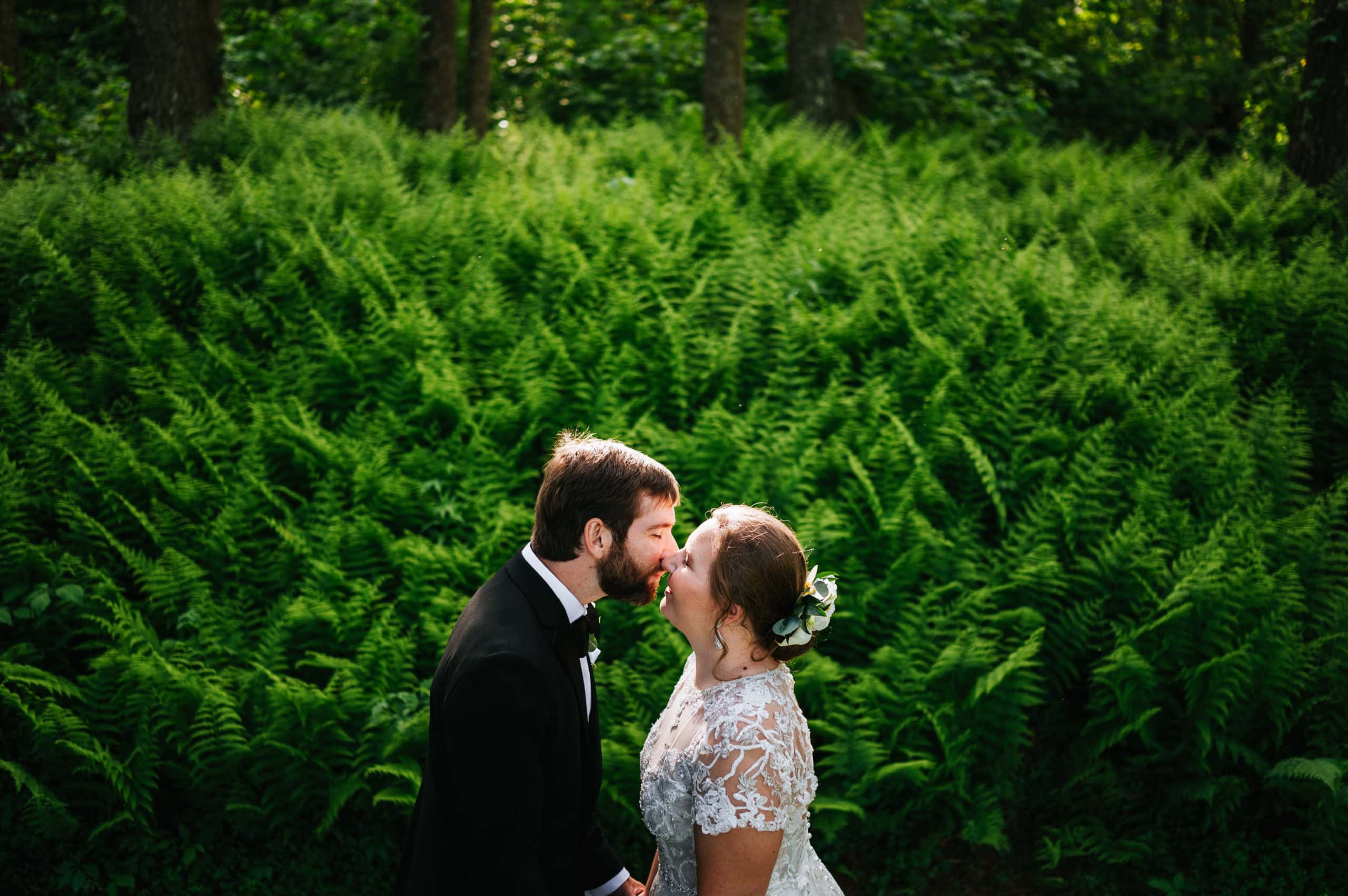 bride and groom kissing in front of ferns